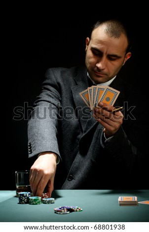 Portrait of a poker player over black background - stock photo