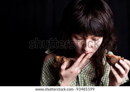 portrait of a poor beggar woman eating bread in her hands - stock photo