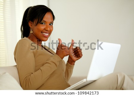 Portrait of a positive afro-American woman in front her laptop while looking at you and lifting the fingers up - stock photo