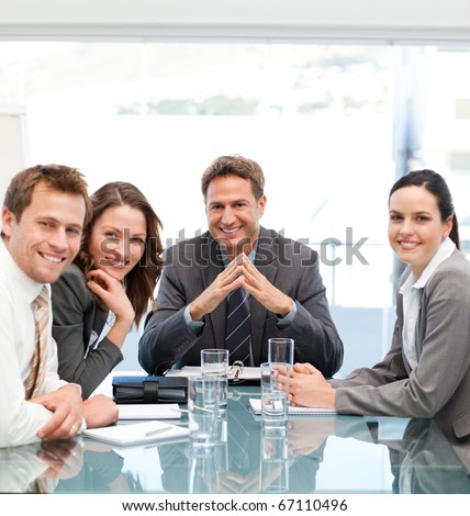 Portrait of a positive manager with his team sitting at a table - stock photo