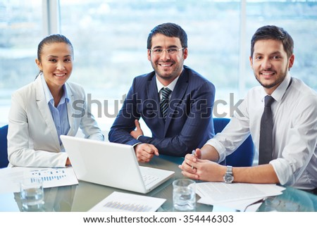 Portrait of a positive team sitting at a table - stock photo