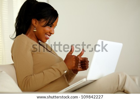 Portrait of a positive young woman looking to laptop screen while sitting on sofa at home indoor and lifting the fingers up - stock photo