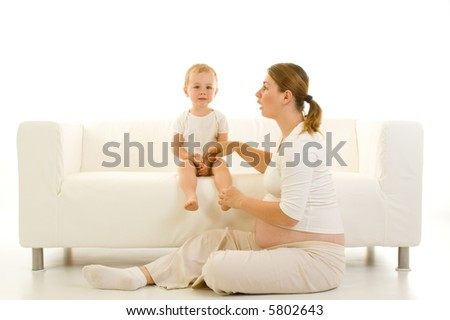 Portrait of a pregnant young mother with her toddler child. Isolated view with white emphasis. - stock photo