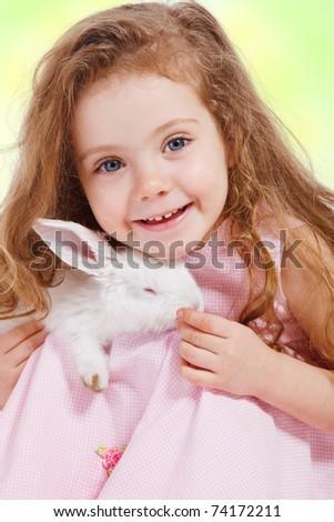 Portrait of a preschool girl holding white rabbit - stock photo