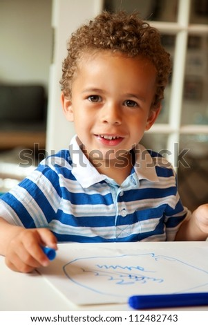 Portrait of a preschooler looking happy after finishing his homework - stock photo