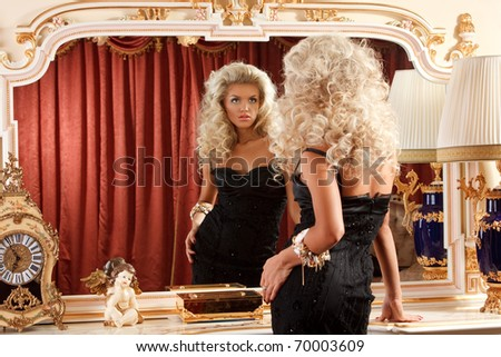 portrait of a pretty blond admiring herself in the mirror - stock photo