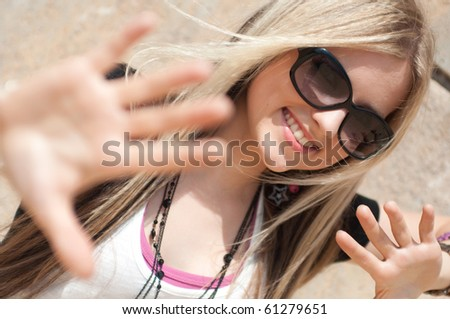 Portrait of a pretty blond girl posing at a wall - stock photo