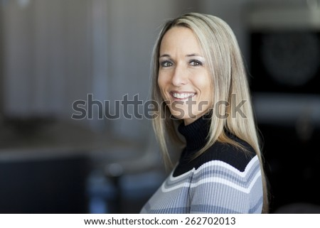 Portrait Of A Pretty Blond Woman Smiling At The Camera - stock photo