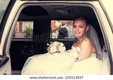 Portrait of a pretty bride in a car. closeup portrait of a pretty shy bride in a car window. bride in the car. wedding bouquet. cheerful face - stock photo