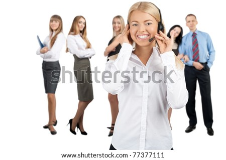 Portrait of a pretty female call center employee with colleagues standing in the background - stock photo