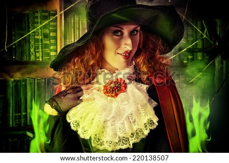 Portrait of a pretty funny witch in the wizarding lair. Fairytales. Halloween. - stock photo