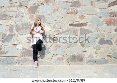 Portrait of a pretty girl at a stone wall - stock photo