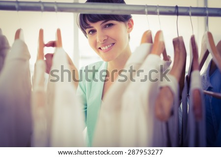 Portrait of a pretty girl looking trough the wardrobe - stock photo