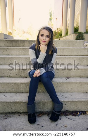 Portrait of a pretty girl sitting on concrete stairs - stock photo
