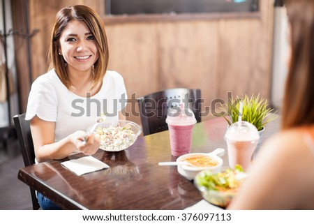 Portrait of a pretty Hispanic young woman eating healthy food with a friend - stock photo