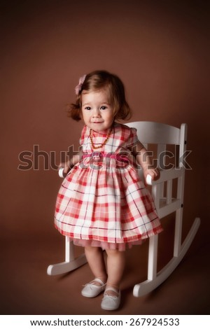 Portrait of a pretty little girl in a rocking chair - stock photo