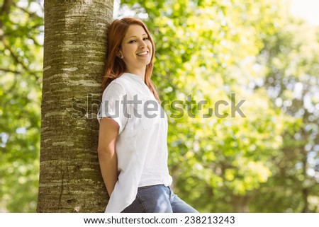 Portrait of a pretty redhead leaning against trunk in green park - stock photo