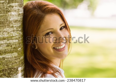 Portrait of a pretty redhead smiling against trunk in park - stock photo
