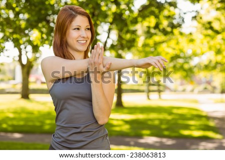 Portrait of a pretty redhead stretching on a sunny day - stock photo