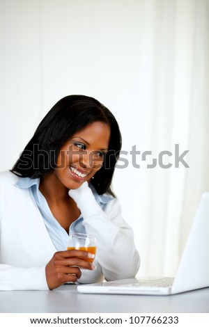 Portrait of a pretty relaxed female smiling and reading on laptop screen at soft composition - stock photo