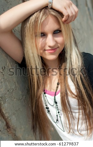 Portrait of a pretty smiling blond girl at a wall - stock photo