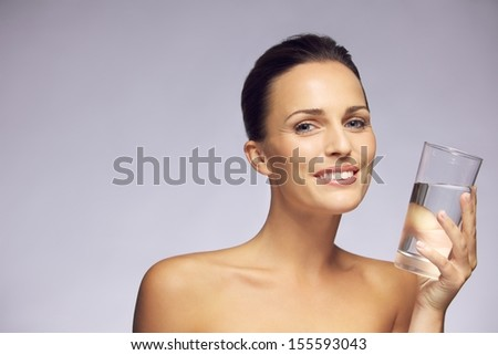 Portrait of a pretty smiling young woman holding a glass of clean water against gray background - stock photo