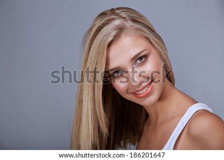 Portrait of a pretty tanned young woman with long blond hair and green eyes on gray background - stock photo
