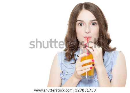 Portrait of a pretty teenage brunette girl posing drinking a fruit juice from a glass using a straw, looking excited, isolated on white background - stock photo