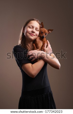 Portrait of a pretty teenager girl with little doggy - stock photo