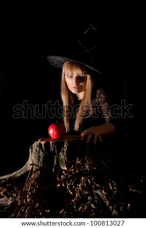 portrait of a pretty witch at stump with apple - stock photo