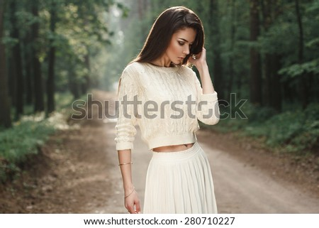 Portrait of a pretty woman in a white sweater on the road in the forest with fog. - stock photo