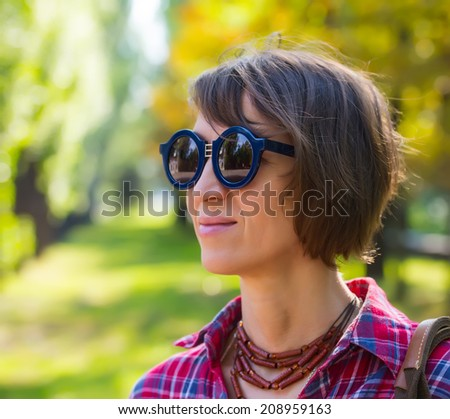 portrait of a pretty woman in sunglasses on background of city park, age forty to forty-five years - stock photo