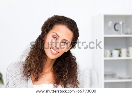 Portrait of a pretty woman standing in her kitchen at home - stock photo