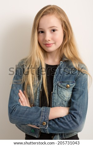 Portrait of a pretty young blond girl in a denim jacket with her arms crossed isolated against a light grey background - stock photo