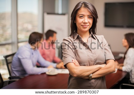 Portrait of a pretty young brunette dressed casual and standing in a meeting room with her co-workers in the background - stock photo