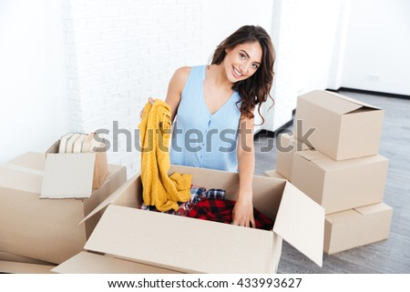 Portrait of a pretty young cheerful girl unpacking in new flat - stock photo