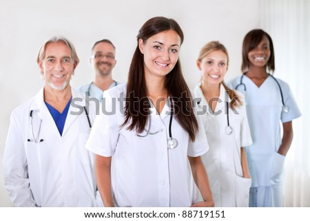 Portrait of a pretty young doctor smiling with colleagues in the background at a hospital - stock photo