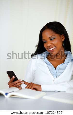 Portrait of a pretty young girl sending a sms with the mobile at soft colors composition - stock photo