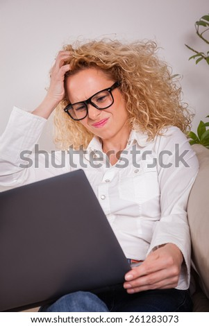 Portrait of a pretty young girl working on her laptop at home - stock photo