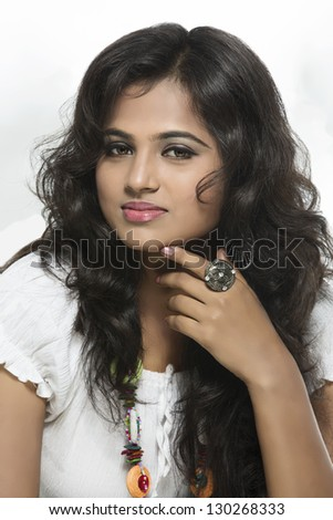 Portrait of a pretty young Indian girl on white background. - stock photo