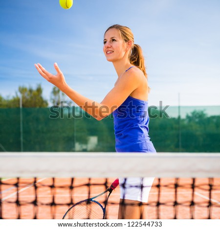 Portrait of a pretty young tennis player - stock photo