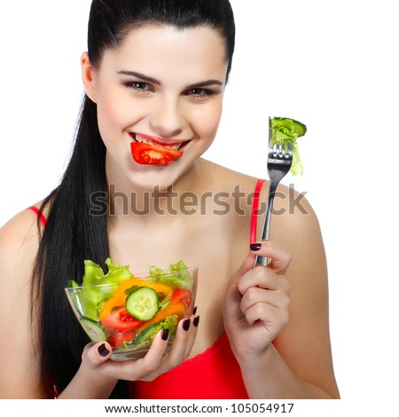Portrait of a pretty young woman eating vegetable salad isolated on  a white background - stock photo