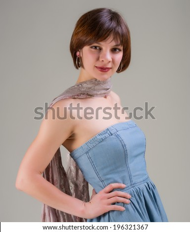 portrait of a pretty young woman in jeans dress and scarf - stock photo