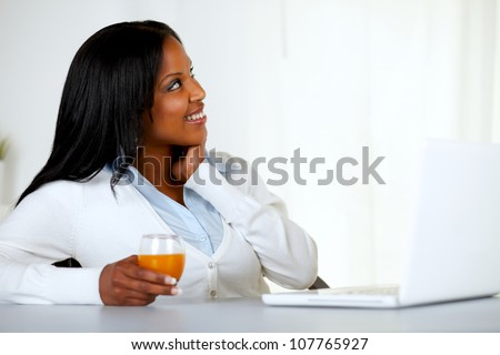 Portrait of a pretty young woman looking up while is holding an orange juice at soft colors composition - stock photo