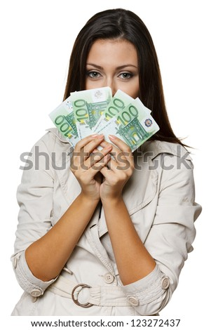 Portrait of a pretty young woman peering at you over a fan of Euro bills - stock photo