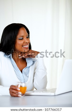 Portrait of a pretty young woman smiling and reading on laptop screen at soft composition - stock photo