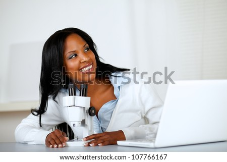 Portrait of a pretty young woman using a microscope and looking to his left at laboratory - stock photo