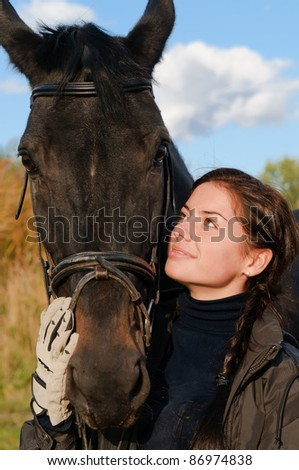 portrait of a pretty young woman with a black horse - stock photo