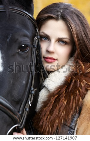 Portrait of a pretty young woman with a black horse riding autumn day - stock photo