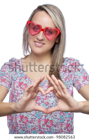Portrait of a pretty young woman with heart-shape sunglasses making heart sign over her heart on white background - stock photo